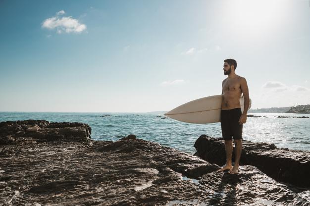 chico guapo a la orilla del mar con tabla de surf