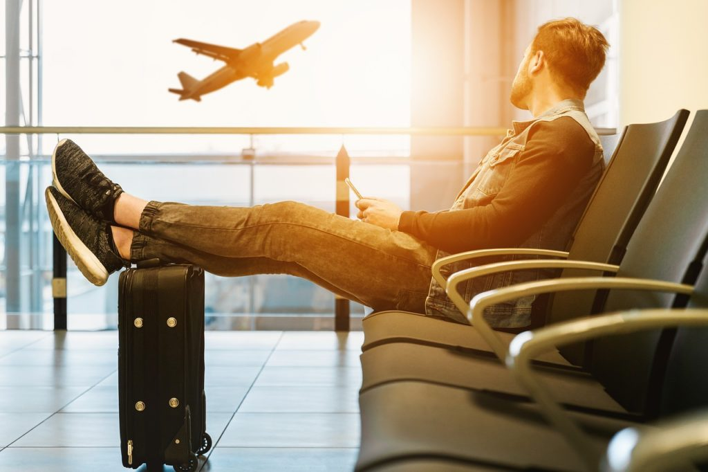 chico esperando su vuelo en el aeropuerto mirando un avión