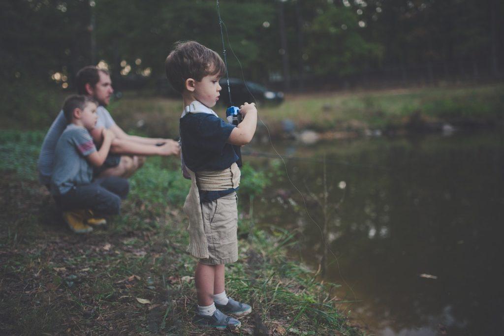 Niño pescando a la orilla de un lago con su familia