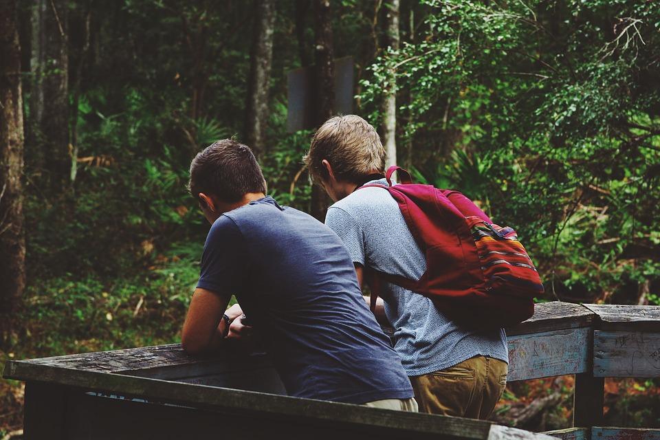 amigos varones jovenes platicando en el bosque